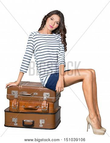 Pretty woman is sitting on old leather suitcase - isolated image
