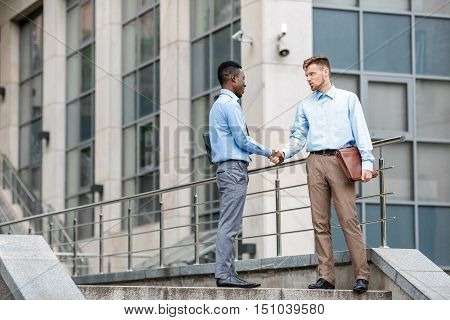 African American businessman and a Caucasian businessman shaking hands on the background of  buildings in the city