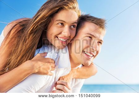 Multiracial people: Happy couple piggybacking cheerful on beach during summer holidays vacation
