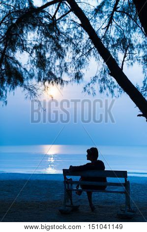 Solitude silhouette woman traveler sitting alone with her bag on retro bench at night on the beach.
