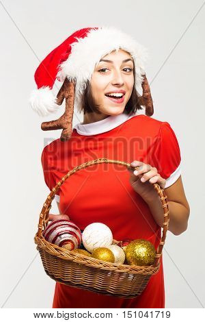 young sexy new year woman or girl with pretty smiling face in red christmas santa claus hat with antlers and holiday costume holds decorative balls in basket isolated on white background
