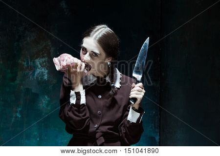 Portrait of a young girl with knife and and a piece of raw meat on a plate. Girl in school uniform as killer. The image in the style of Halloween