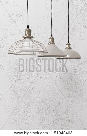 Many industrial pendant lamps against white rough wall