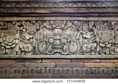 Close up view of carved stone fence of traditional Hindu temple with demon guard in Indonesia, Bali.