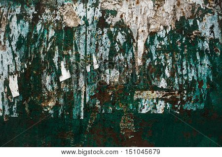 old metal rusty abstract wall with bunch of ads that hang on it and worn green paint
