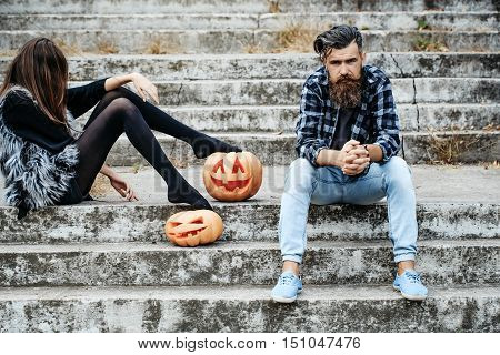 young halloween couple of bearded man with beard and mustache and girl in black tights sitting on stony stairs with traditional autumn holiday symbol of orange spooky pumpkin sunny outdoor