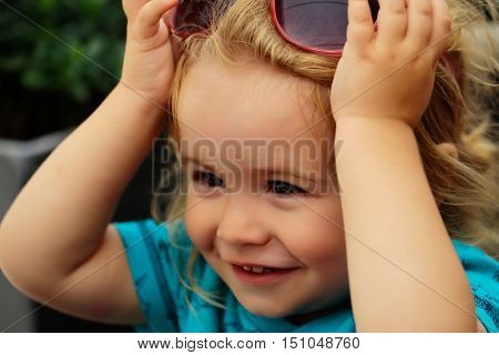 Funny baby boy child with curly blond hair and sunglasses on summer day at outdoor cafe