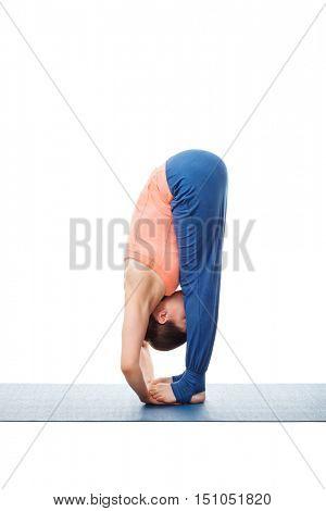 Woman doing Ashtanga Vinyasa Yoga asana Padahastasana - standing forward bend with hand under feet pose posture isolated on white background