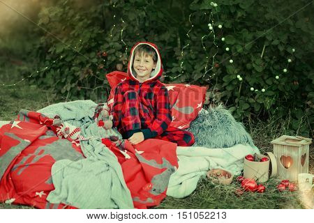 outdoors little boy sitting in bed in red pajamas with toys and fruit