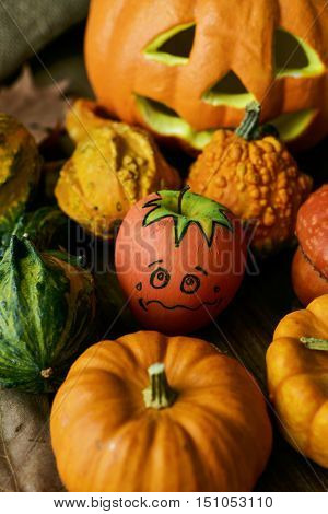 an apple disguised as a pumpkin with a funny face trying to go unnoticed between different real pumpkins