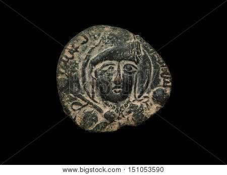 Ancient Copper Islamic Coin With Face On It Isolated On Black