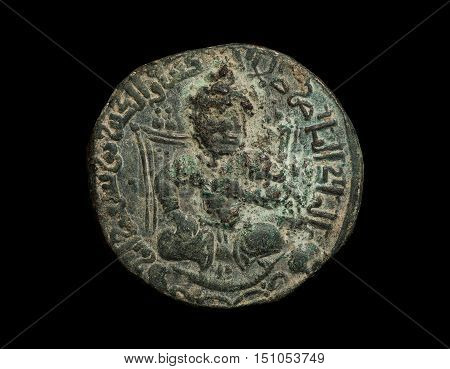 Ancient Bronze Islamic Coin With Seated Figure Isolated On Black