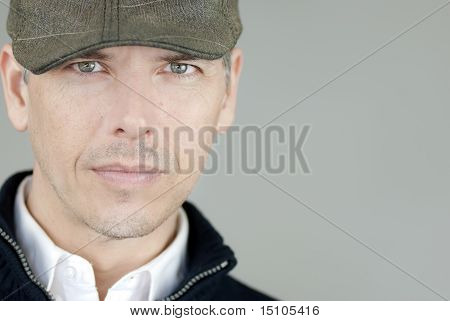 Confident Man In Newsboy Hat Looks To Camera