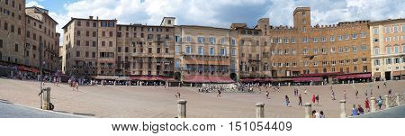 SIENA, ITALY- AUGUST 30, 2016: wide angle panorama of Piazza del Campo, in the old city center of Siena, world famous for the historical Palio; many tourists are walking along the square, in the background the facade of the medieval palaces.