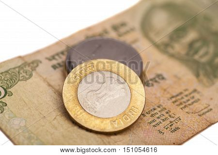 Indian Currency Rupee Notes and Coins on white background.
