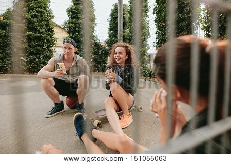 Group of friends sitting at outdoor basketball court eating and having fun. Teenagers relaxing basketball court.