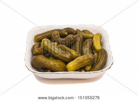 Pickled cucumbers on a plate isolated on white