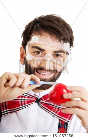 Determined man cutting heart model with scalpel.