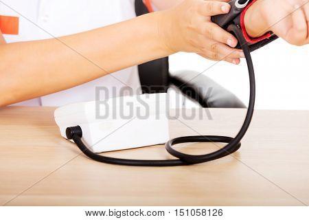 Doctor sitting behind the desk holding blood pressure gauge