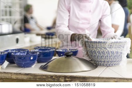 Caterer preparing food on a buffet at a restaurant or venue closeup of her gloved hands removing plastic covering on food