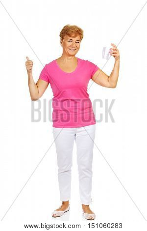 Smiling senior woman holding a tooth model and showing thumb up