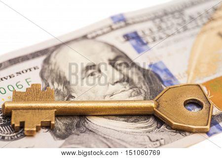gold key on hundred dollar bill isolated on white