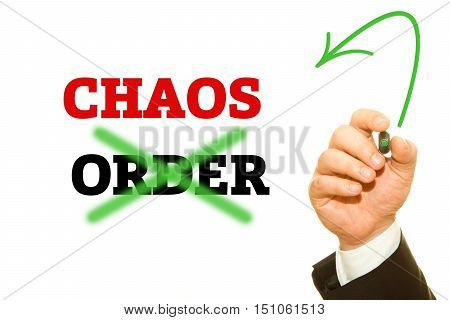 Hand writing CHAOS and ORDER word on a transparent wipe board.