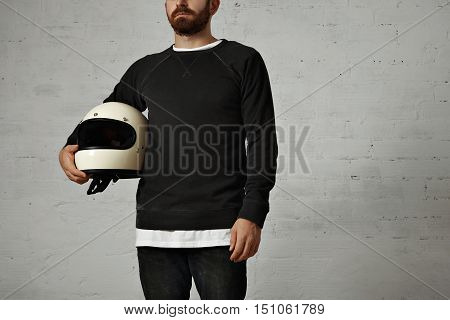 Portrait of a bearded young man in unlabeled blank cotton sweatshirt holding a white motorcycle helmet isolated on white