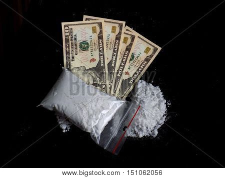 Cocaine bag, pile and dollar money bills on black background