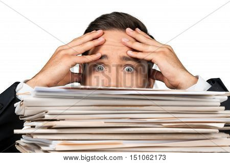 Closeup of a Worried Employee Behind Stack of Folders