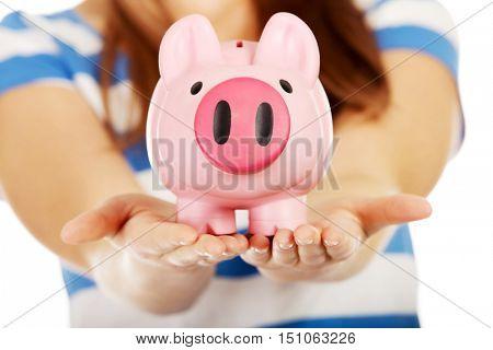 Teenage woman holding pink piggybank