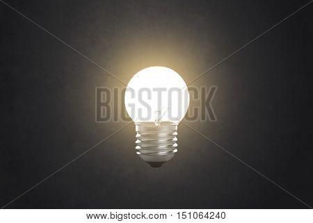 lit glowing yellow tungsten light bulb on black background.