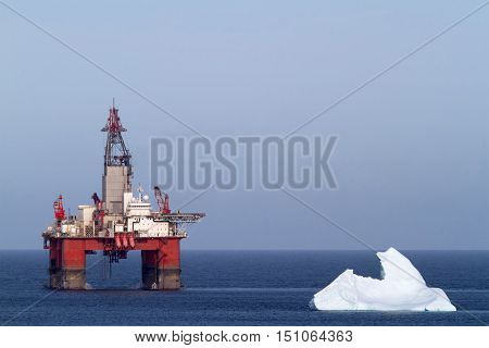 Iceberg next to a offshore oil drilling platform.