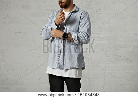 Bearded hipster unbuttoning and rolling up the second sleeve of his casual faded blue denim shirt in a studio with white walls