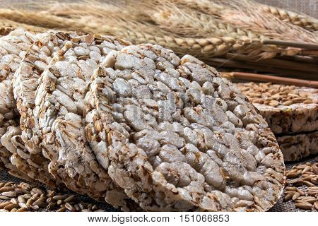 Puffed wheat cake and grains of wheat on the background of wheat ears