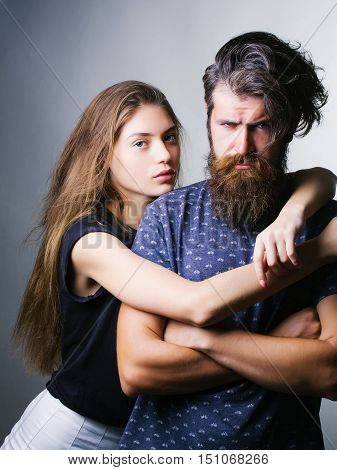 Young pair of pretty serious woman in black clothes hugging by hands man hipster with beard on his handsome frown face in dark blue studio on gray background