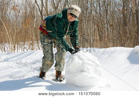 woman rolls a snowball in the forest