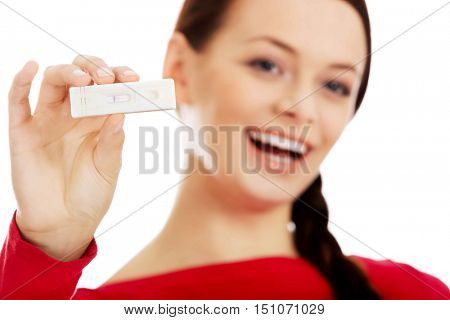 Happy young woman shows positive pregnancy test