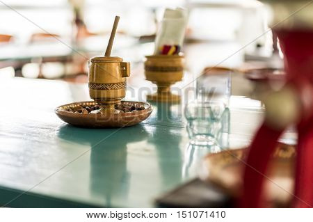Wooden mortar beside mincing machine on kitchen table with obscured background
