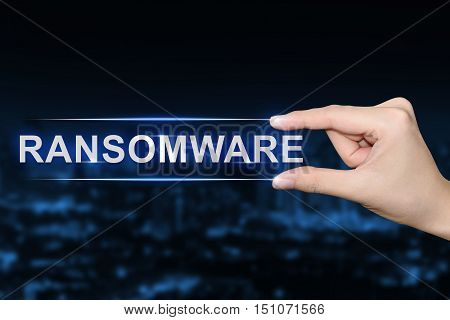 hand pushing ransomware button on blurred blue background