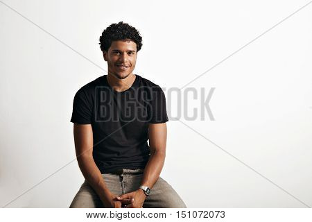 Friendly smiling attractive young man in unlabeled cotton black t-shirt and jeans sitting on a chair and looking into camera isolated on white