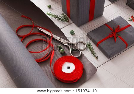 Gift wrapping background. Packaging modern christmas present. Lots of gift boxes in stylish modern gray paper, decorated with red satin ribbon bows. Christmas and winter holidays concept