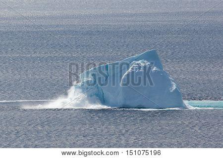 Newfoundland coastal iceberg collapsing and producing waves.