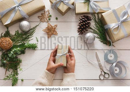 Gift wrapping. Beautiful handmade christmas present, box in stylish paper with satin silver ribbon. Top view of hands on white wood table with fir tree branches, modern decoration, high-key