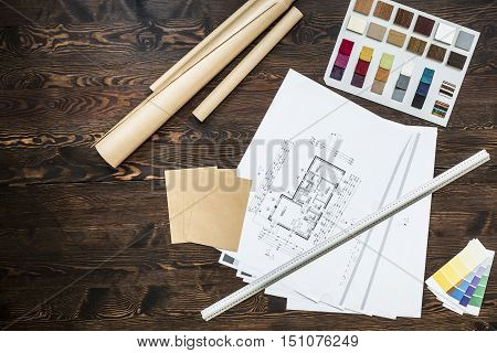 Wooden desk of architect with architectural projects color pickers and ruler on