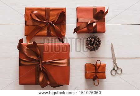 Lots of gift boxes and pine cone on white wood background. Stylish modern presents in maroon paper decorated with satin ribbon bows. Christmas and winter holidays concept, top view, flat lay