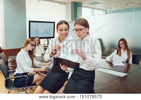 Asian and European business women standing on the team's background and study documents