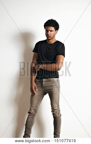 Full body shot of an upset looking frowning attractive black young man in a plain black t-shirt and skinny grey jeans isolated on white