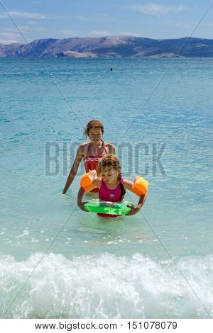 Two Sisters Playing Games And Swimming In The Sea