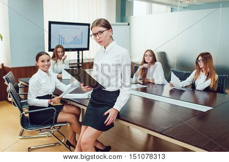 Beautiful business woman on the team's background with documents in hand